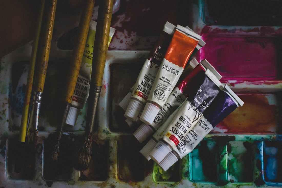 photo of acrylic paint soft tubes beside paintbrushes